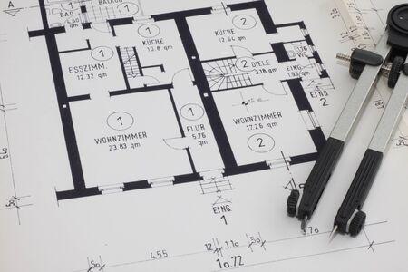 A blueprint with pocket calculator and a folder