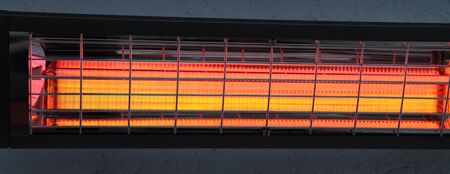 A switched on infrared heater on a house wall