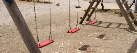 An empty swing on a playground