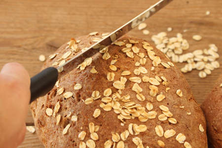 two fresh farmer's breads with a knife