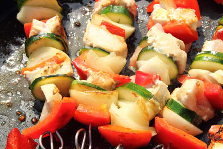 delicious shish kebab skewers in the pan with peppers and onions