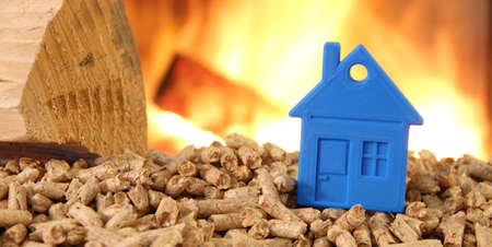 Wood stove with pellets with a toy house against fire