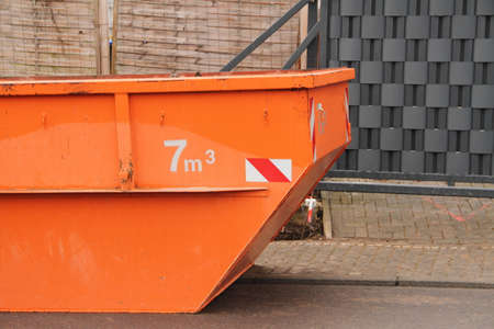 an old orange construction waste container on the street