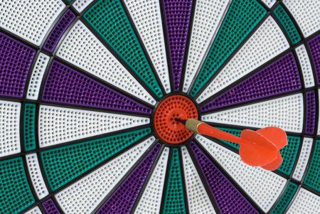 Dartboard with dart in center (bullseye)