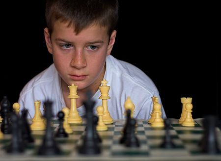 Boy playing chess on black background photo
