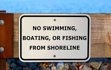 No swimming, boating, or fishing from shoreline sign at a reservoir Banco de Imagens