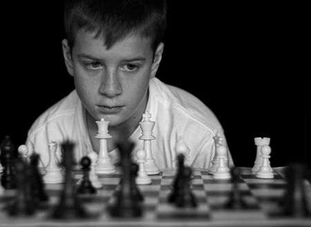 Boy playing chess on black background