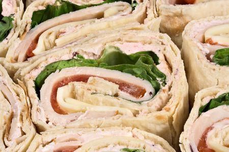 A sliced turkey wrap sandwich Imagens