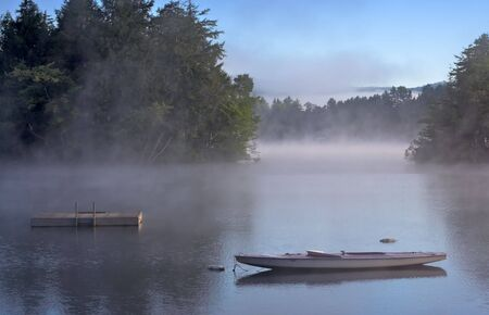 Early morning fog on a lake. A boat and dock are in the foreground.