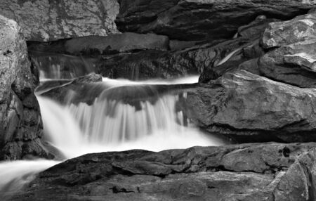 A small waterfall in a stream flowing down rocks photo