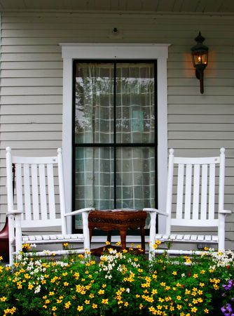 A porch with two chairs and a flower bed