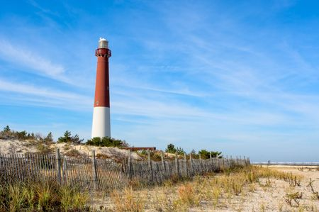 A lighthouse on the beach. There is also an old wooden fence on the beach in this landscape. This is Barnegat Lighthouse, nicknamed