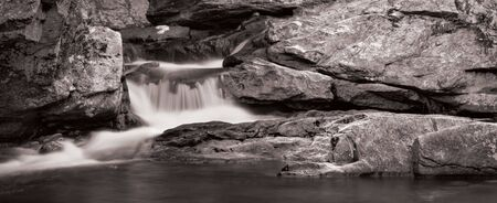 A small waterfall over rock in panorama format. Photo is in black and white. photo