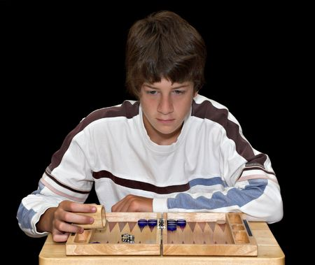 A young teenage boy playing a game of backgammon. The boy and board are isolated over a black background.