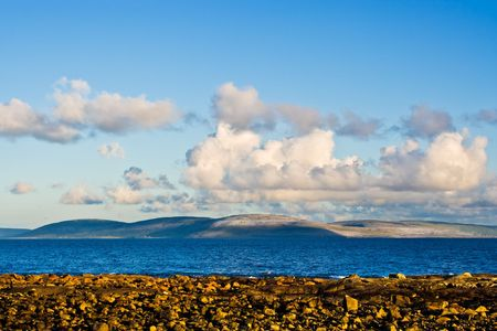 Galway Bay in Ireland from the town of Spiddal with The Burren across the bay. Photo is layered from front to back with Rocks, Galway Bay, The Burren, and sky. Imagens
