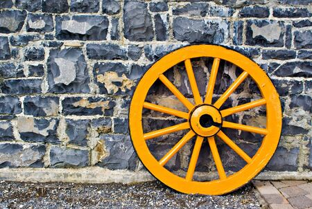 An old yellow wooden wagon wheel leaning against a stone wall