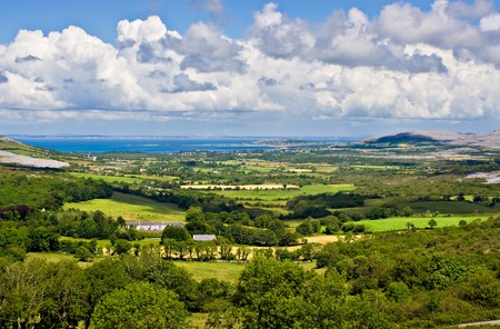 Landscape of County Clare, Ireland. Green fields in foreground and Galway Bay in the background. Beginings of the Burren can also be seen. Stock Photo - 1391230