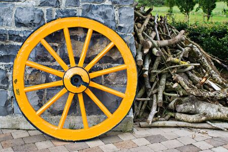 old wood farm wagon: An old antique yellow wooden wagon wheel leaning against a stone wall. There is a pile of tree branches laying next to it. Stock Photo