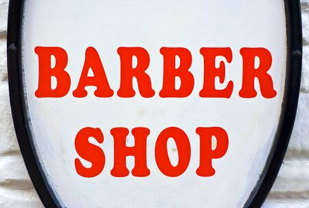 A Barber Shop sign with red letters and a white background Stock Photo - 1479665
