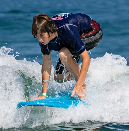 A teenager surfing. The boy is just beginning to stand up on the surfboard.