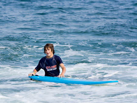 bodyboard: A teenage boy standing in the ocean with his surfboard