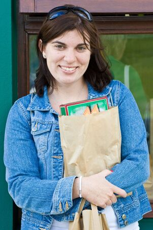 purchased: An attractive young lady standing outside a store. She is holding a package that she just purchased. Stock Photo