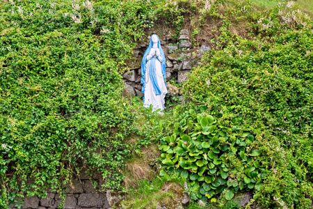紅葉に囲まれた丘の聖母マリアの像 写真素材