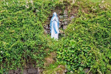 단풍에 둘러싸인 언덕에 성모 마리아의 동상 스톡 콘텐츠
