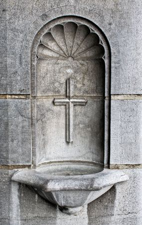A cross and holy water well as part of the architecture in a cathedral Фото со стока