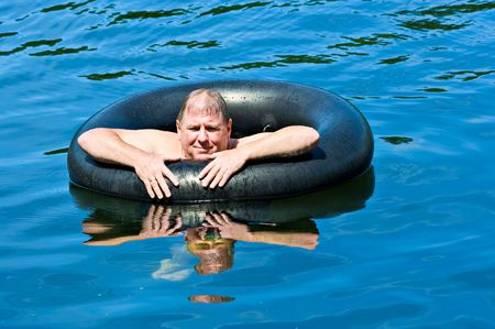 A man in water floating on an inner tube