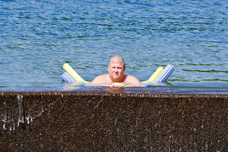 soaks: A adult man cooling off in a lake