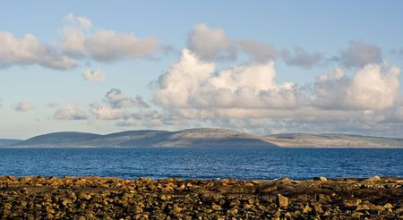 Galway Bay in Ireland from the town of Spiddal with The Burren across the bay. Photo is layered from front to back with Rocks, Galway Bay, The Burren, and sky. Stock Photo - 2939742