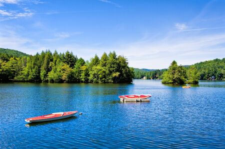 tranquillity: A lake in the mountains with small boats Stock Photo