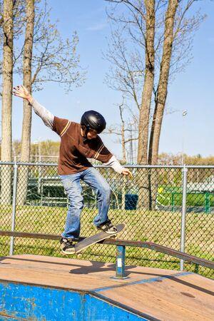A teenage boy skateboarding at a park Imagens