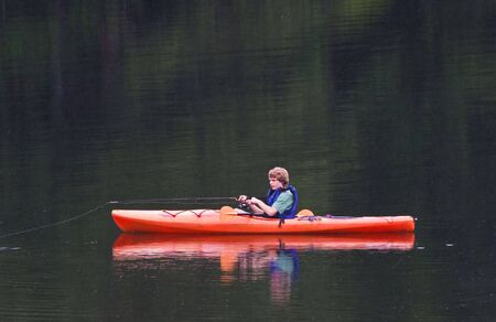A young teenage boy fishing from a kayak in the evening. It is raining and streaks of rain can be seen against the lake background. photo