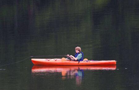 kayak: Een jonge tiener jongen vissen vanuit een kajak in de avond. Het regent en strepen regen kan worden gezien tegen de achtergrond meer.