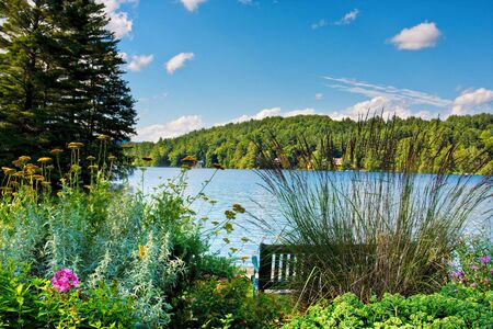 A scenic lake in the mountains. There is a bench and a flower garden in the foreground. Imagens