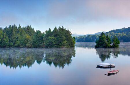이른 아침에 물에 안개와 호수. 보트와 독이 전경에 있습니다.