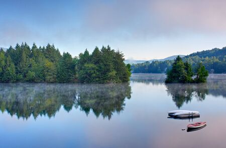 sunrise lake: A lake in the early morning with fog on the water. A boat and dock are in the foreground.