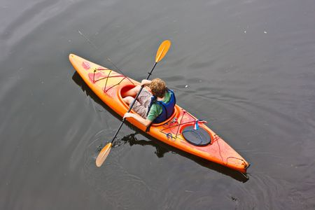 fishing pole: A teenage boy paddling a kayak on a lake. There is a fishing pole in the kayak with him.