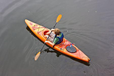 Een tiener jongen poedelbad een kajak op een meer. Er is een visserij-pool in de kajak met hem.