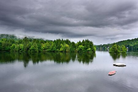uğursuz: A lake during a rain storm. There are dark, ominous rain clouds overhead