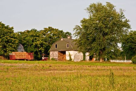 A barn in the country with a trailer full of hay. was captured in late evening sunlight. Stock Photo - 5240462