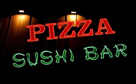 A Pizza and Sushi Bar neon sign in front of a restaurant 版權商用圖片