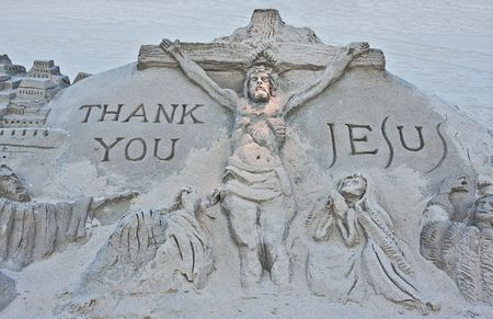 A sand sculpture on a beach of the crucifixion of Jesus photo