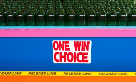 A game at the boardwalk where you toss rings trying to land them around the necks of bottles  The photo has rows of bottles as well as a sign that says One Win Choice in a colorful display  photo