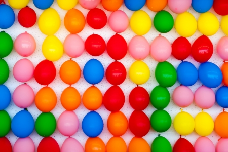 ARCADE GAMES: A white wall with colorful balloons attached  Photo is of a boardwalk arcade game where you throw darts and try to pop balloons  Only the wall of balloons is shown