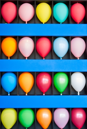 A blue wall case with colorful balloons  Photo is of a boardwalk arcade game  Only the wall case and balloons are shown