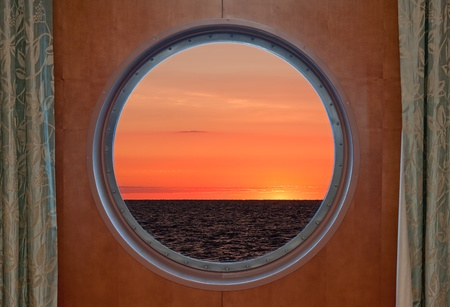 sunsets: View of a sunrise through the porthole of a cruise ship