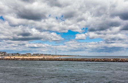 Wide angle photo of the New Jersey Shore  The ocean, inlet, jetty, beach, town, and sky are shown in the New Jersey seaside town of Manasquan